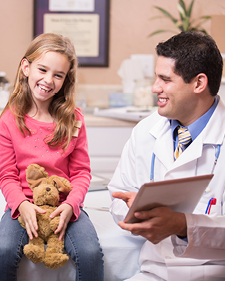 Happy child sitting with a brown bear next to a doctor