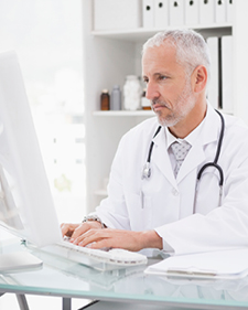 Elderly doctor using a desktop computer looking serious