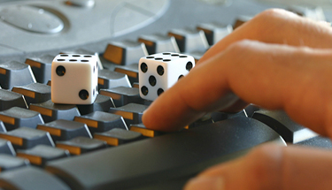 Two dice sitting on top of a keyboard being used