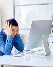 Frustrated man in blue button up on desktop computer