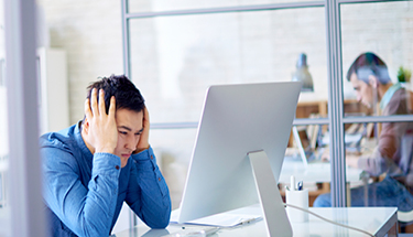Frustrated man in blue button up on desktop computer in office