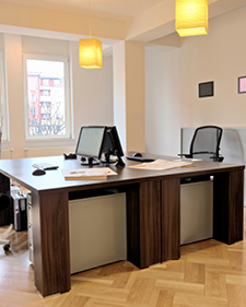 Two desks with desktop computers in a large office