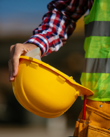 Construction worker holding a yellow hard hat on their side
