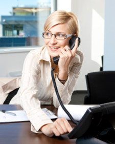 Happy business woman in glasses using phone