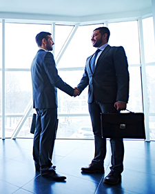 Two people shaking hands while holding briefcases in hallway